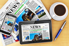 Tablet computer, smartphone and newspapers Royalty Free Stock Photos