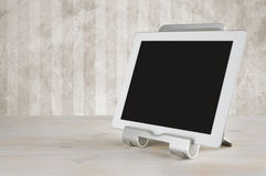 Tablet computer in the stand on table over grunge wall Royalty Free Stock Image