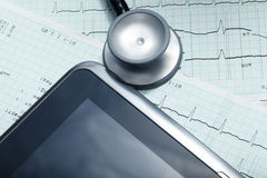 Tablet computer, stethoscope, cardiogram. Stock Photo