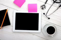 Tablet computer with stethoscope and other tools on wooden backg Stock Photos