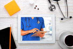 Tablet computer with stethoscope and other tools on wooden backg Stock Image