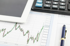 Tablet-Computer, Taschenrechner, Stift und Finanzdiagramm auf weißem Hintergrund Lizenzfreies Stockfoto