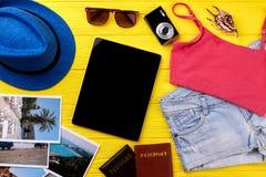 Tablet computer between travel accessories. Stock Photo