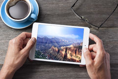 Tablet Computer Vacation Grand Canyon. A tablet computer with a Grand Canyon photo on the screen with coffee cup and glasses. Grand Canyon image is available on Stock Image