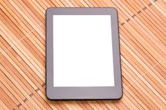 Tablet computer with a white screen under the text. Tablet computer on a wooden background stock photo