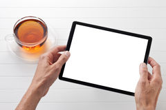 Tablet Computer White Tea. Hands holding a tablet computer on a white background with a cup of tea Stock Images