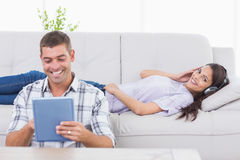 Tablet computer while woman listening music on headphones. Happy men using tablet computer while women listening music on headphones at home Royalty Free Stock Photo