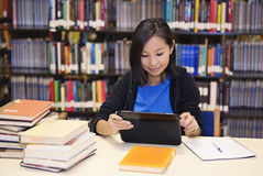 Tablet computer woman. Smiling asian  student using a tablet computer in a library Stock Images