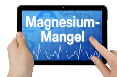 Tablet comTablet computer with the german word for magnesium deficiency puter with the german word for addiction care - Suchthilfe royalty free stock image