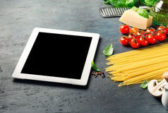 Tablet with copy space with Ingredients for cooking Italian past Royalty Free Stock Photos