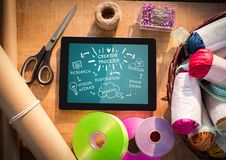 Tablet on craft table showing white design doodles against teal background Stock Image