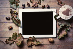 Tablet, cup of coffee and fallen leaves Stock Photography