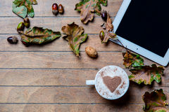 Tablet, cup of coffee and fallen leaves Royalty Free Stock Photography