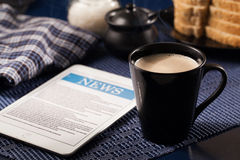 Tablet and cup of coffee. Morning news with tablet and cup of coffee royalty free stock images