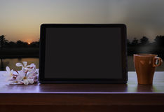 Tablet  and a cup of coffee during sunset Royalty Free Stock Photo