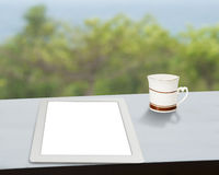 Tablet with cup of coffee on table with nature view Stock Image