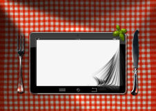 Tablet and Cutlery on a Table with Tablecloth Stock Image