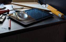 Tablet On A Dark Cupboard Surrounded by Tools In A Dirty Basement Stock Photos