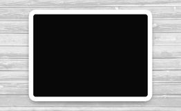 Tablet with the dark screen on wooden background. stock illustration