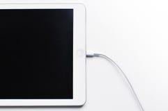 Tablet, das auf weißem Hintergrund auflädt Lizenzfreie Stockfotos