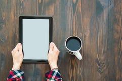 Tablet in den H?nden auf dem Boden und einem Tasse Kaffee dazu stockfotografie
