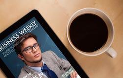 Tablet den PC, der Zeitschrift auf Schirm mit einem Tasse Kaffee auf einem d zeigt Lizenzfreie Stockfotos