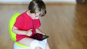 Tablet Dependence. Boy on potty using tablet pc stock video footage