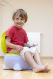Tablet Dependence. Boy on potty using tablet pc Stock Image