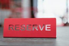 Tablet der roten Farbe auf einer Tabelle in einem Restaurant mit einer Unterzeichnungsreserve Stockfotos