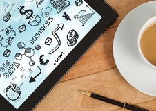 Tablet on desk with coffee showing black business doodles and sky Royalty Free Stock Photography