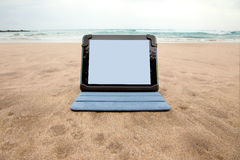 Tablet device on beach Royalty Free Stock Photos