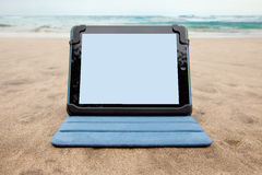 Tablet device on beach Royalty Free Stock Images