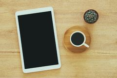 Tablet device with black screen next to cup of coffee over wooden desk. Stock Photo