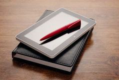 Tablet Device on Notebook at Wooden Table Stock Images