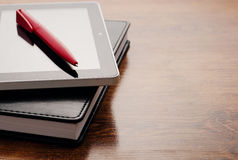 Tablet Device on Notebook at Wooden Table Stock Photography