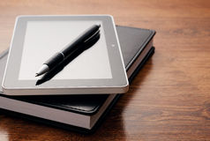 Tablet Device on Notebook at Wooden Table Royalty Free Stock Image