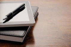 Tablet Device on Notebook at Wooden Table Royalty Free Stock Photo