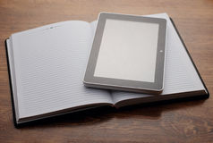 Tablet Device on Open Notebook at Wooden Table Royalty Free Stock Image