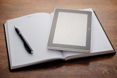 Tablet Device on Open Notebook at Wooden Table Stock Photo