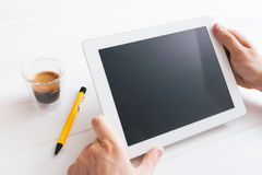Tablet device over a white wooden workspace table στοκ φωτογραφία
