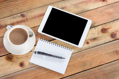 Tablet device on wooden workspace table Royalty Free Stock Images
