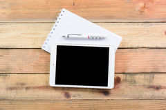 Tablet device on wooden workspace table Stock Photo