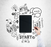 A tablet, digital device is surrounded by drawn business icons. A hand is drawing a bar chart. Stock Photo
