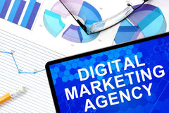 Tablet with digital marketing agency, graphs and glasses. Stock Photo
