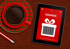 Tablet with discount coupon and  cup of coffee lying on desk Royalty Free Stock Photography