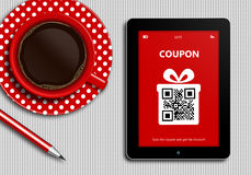 Tablet with discount coupon and  cup of coffee lying on tableclo Stock Photos