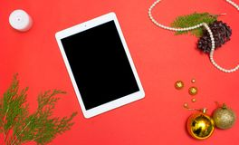 Tablet display on table on red screen for mockup in Christmas time. Christmas tree, decorations in background. Tablet display on table on red screen for mockup Stock Photos