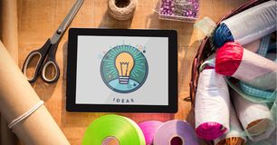 Tablet displaying ideas light bulb on table with sewing materials royalty free stock photography