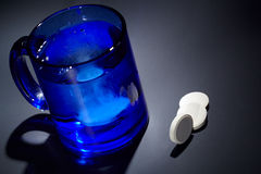 Tablet dissolving in a blue glass of water. Royalty Free Stock Photo