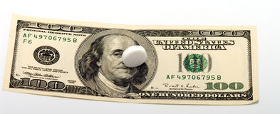 Tablet and dollars. Pill on a note one hundred dollars Stock Image